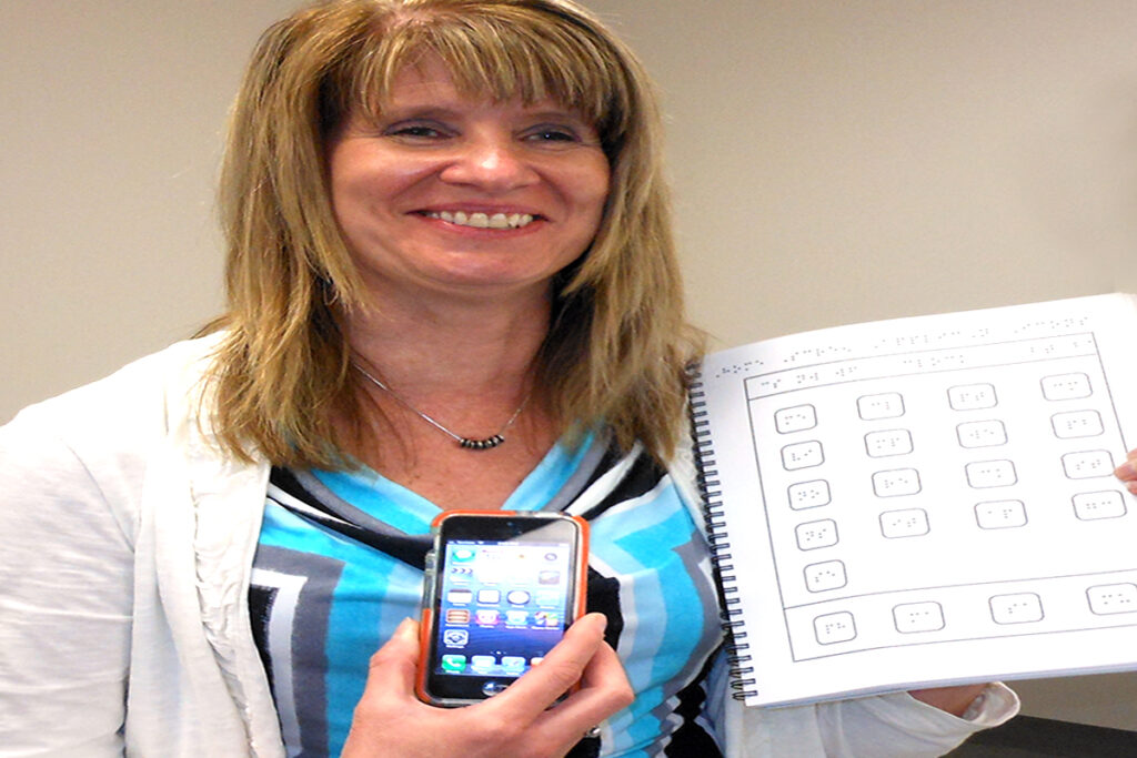 Picture of a woman with vision loss with a smart phone and a braille book