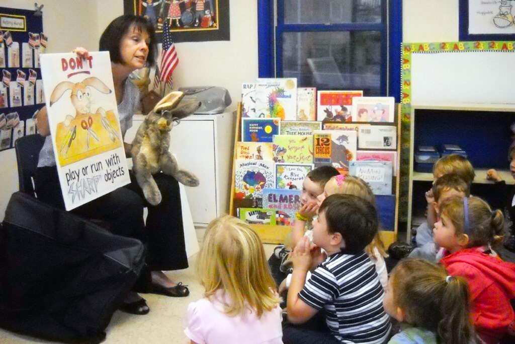 Picture of an agency team member presenting the C. Well Bunny program to children