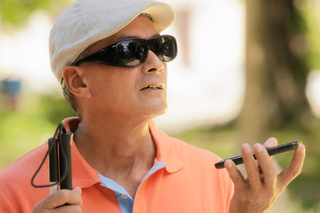 Photo of a man with a visual impairment using a smartphone