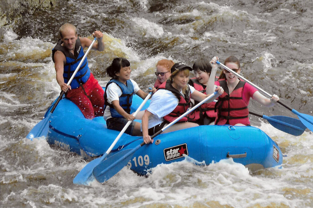 Picture of kids and counselors whitewater rafting as part of our Camp I CAN! program for kids