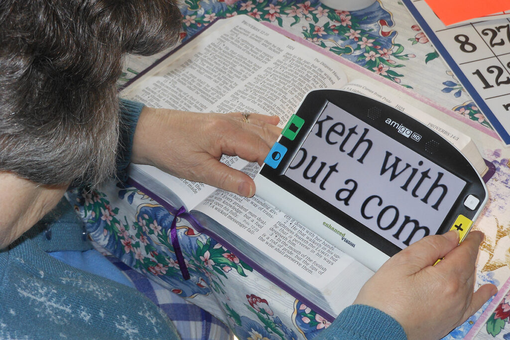Photo of a client with a handheld digital magnifier