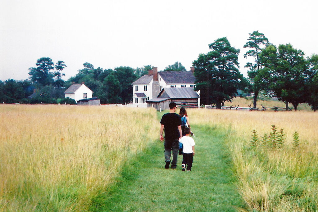 Photo of a family walking within a farm landscape