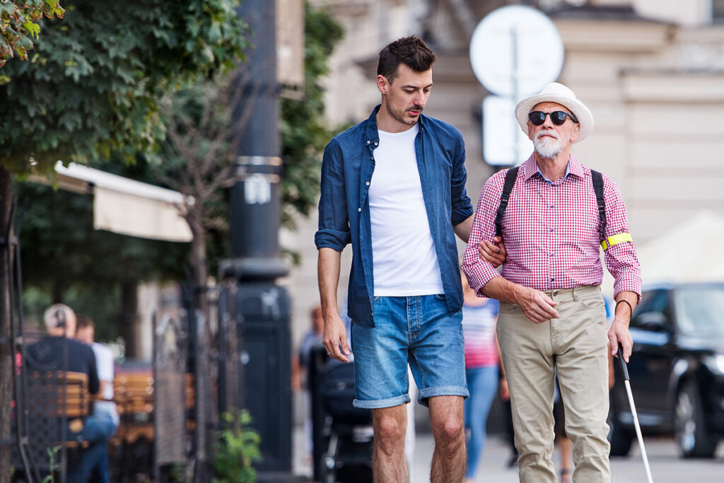 Photo of a man using sighted guide techniques to help a man with vision loss