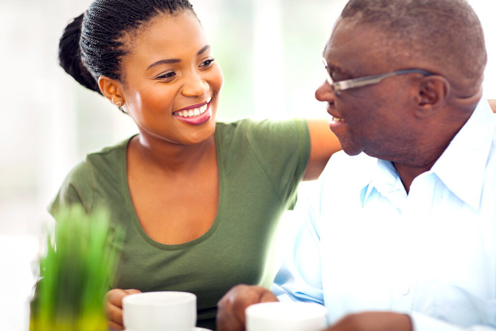 Photo of an older African-American man enjoying coffee with his granddaughter
