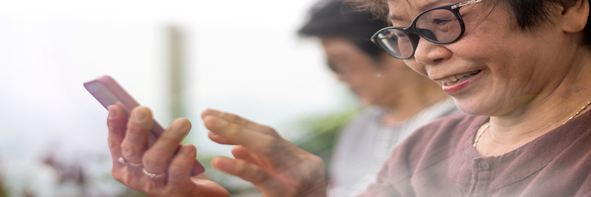 Photo of an older woman with glasses looking at a smartphone