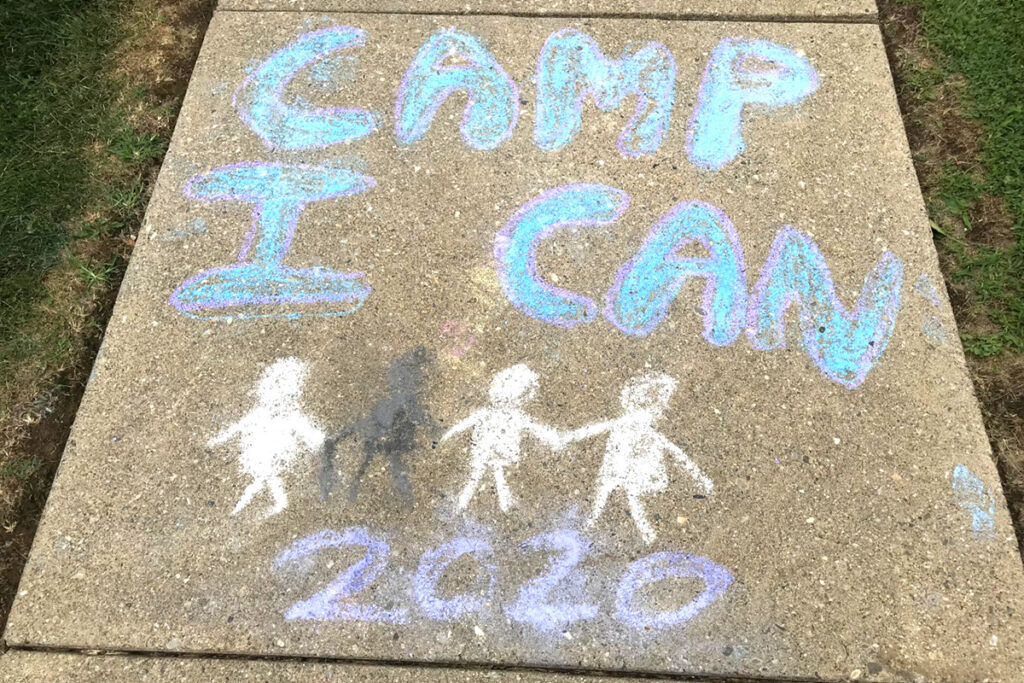 A chalk drawing of the Camp I CAN! 2020 graphic on a sidewalk panel