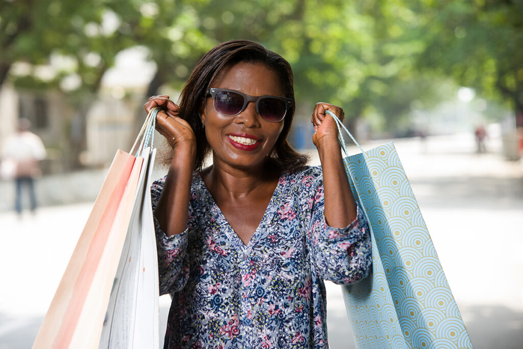 Photo of a woman who is visually impaired holding shopping bags