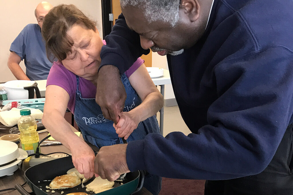Photo of two people making pancakes during a previous breakfast cooking class