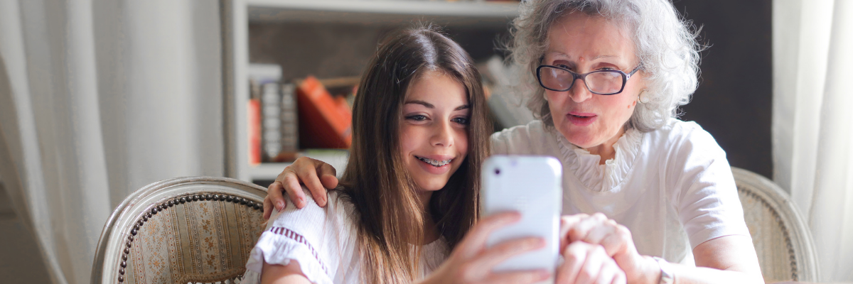 Photo of an older woman and a young girl looking at smartphone