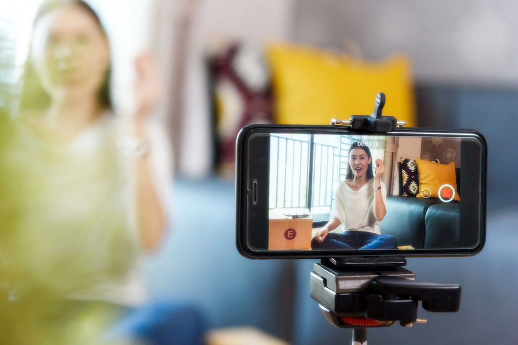 Photo of a woman recording a video for social media with a smartphone