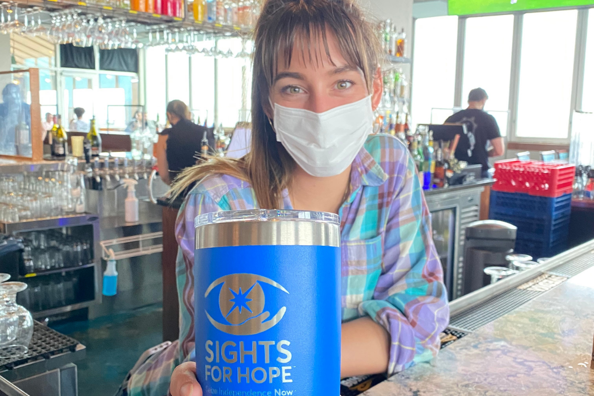 Photo of a woman holding a blue YETI tumbler branded with the Sights for Hope logo