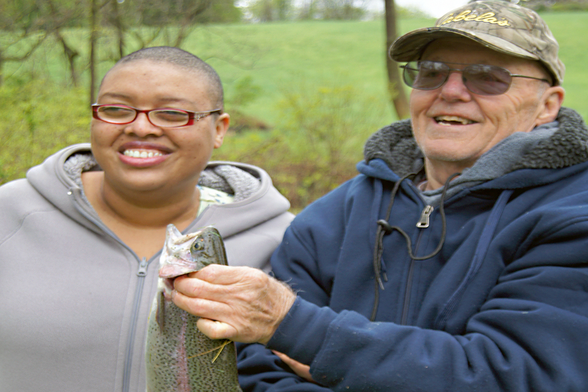 Photo of a Lions Club member and a client showing off a fish that they caught