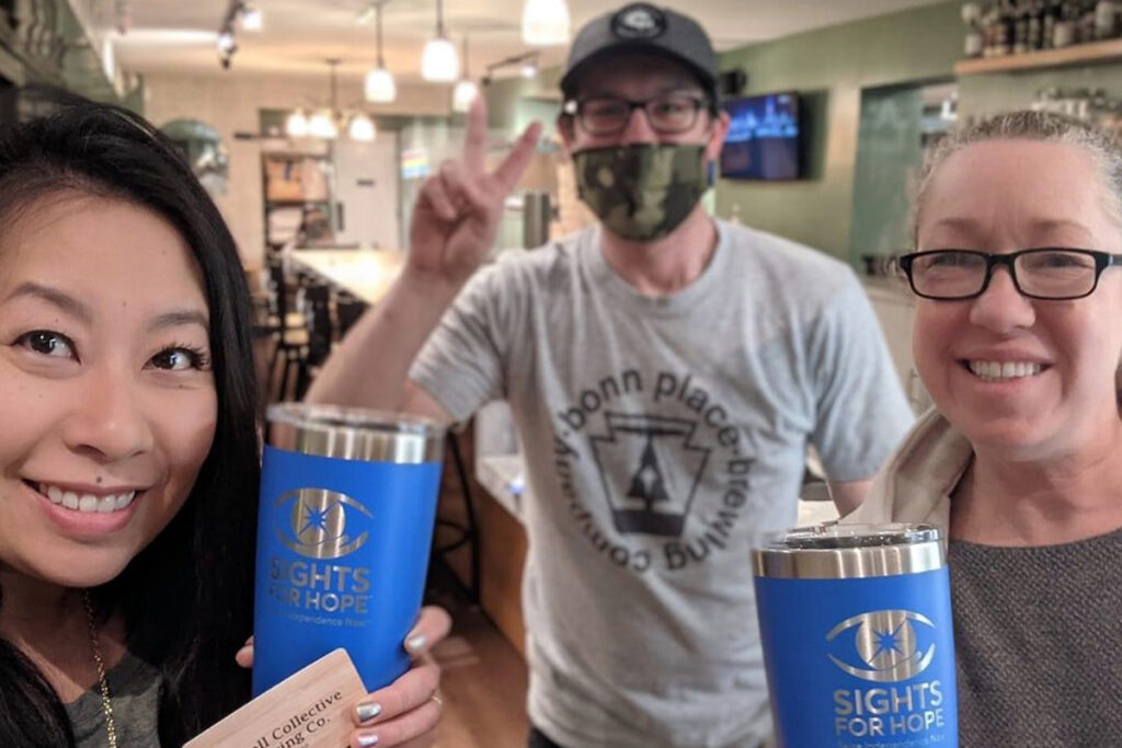 Photo of two people holding Sights for Hope tumblers at McCall Collective Brewing Company
