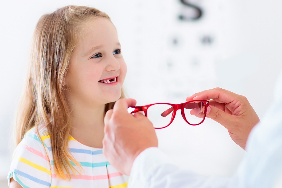 Image of a pre-kindergarten girl being fitted for glasses by an eyecare professional