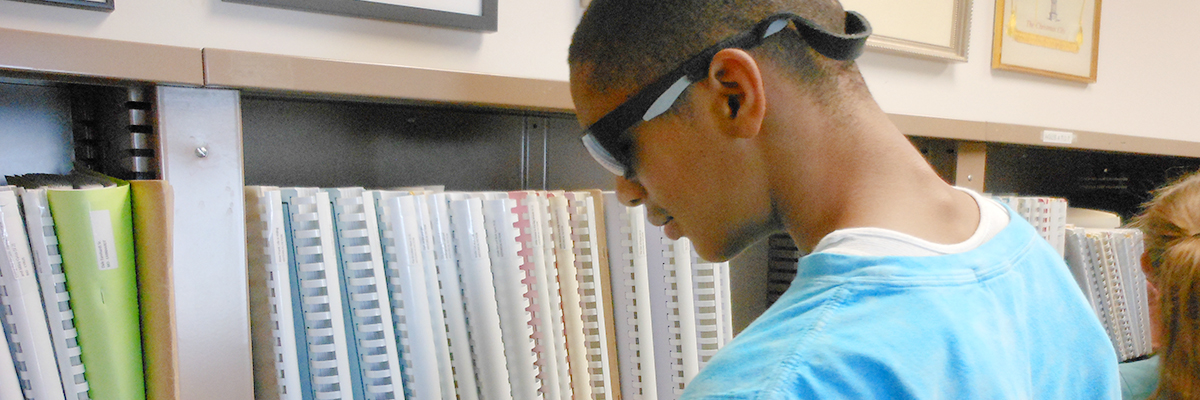Photo of a young man browsing books in the Posch Braille Library
